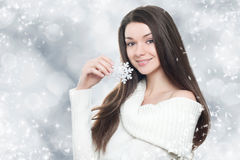 Beautiful young brunette woman with silver snowflake. On winter background royalty free stock photos