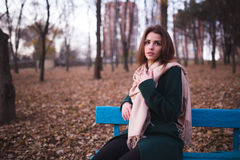 Beautiful young brunette woman sitting on a bench in autumn park Royalty Free Stock Photos