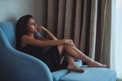 Woman sitting on the chair and looking through the window. Beautiful young brunette woman sitting on the chair and looking through the window Stock Photos
