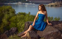 Beautiful young brunette woman sitting on a cliff above the river. Beautiful young brunette woman, wearing blue dress, sitting on a cliff above the river with Stock Photography