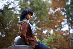 Beautiful young brunette woman sitting in park Royalty Free Stock Photography