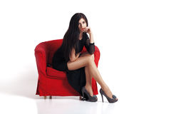 Beautiful young brunette woman sitting on red chair Royalty Free Stock Photos