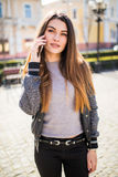 Beautiful young brunette woman speaking on the smart-phone at the city street background. Royalty Free Stock Photography