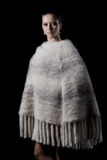 Beauty female model wearing warm white knitted poncho Royalty Free Stock Image