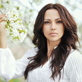 Beautiful young brunette woman standing near the apple tree - cl Stock Images