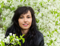 Beautiful young brunette woman standing near the apple tree. Stock Photo