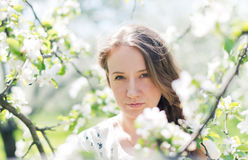 Beautiful young brunette woman standing near the apple tree Royalty Free Stock Photography