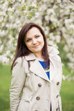 Beautiful young brunette woman standing near the blossoming apple tree on a warm spring day Royalty Free Stock Image