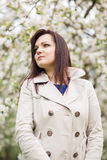 Beautiful young brunette woman standing near the blossoming apple tree on a warm spring day Stock Photography