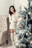 Beautiful young brunette woman standing near fir tree in Christm Royalty Free Stock Image