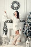 Beautiful young brunette woman standing near fir tree in Christm Stock Photography