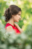 Beautiful young brunette woman standing near white blossom Stock Photos