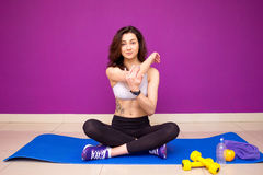 Beautiful young brunette woman stretching the muscles of her arms and bac. Smiling sporty girl doing yoga practice, asana for stre Royalty Free Stock Images
