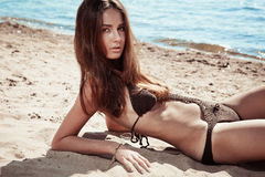 Beautiful young brunette woman on a sunny beach Royalty Free Stock Images