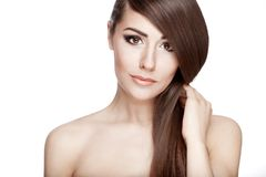 Beautiful young brunette woman touches her hair Stock Images