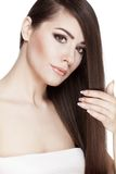 Beautiful young brunette woman touches her hair Stock Photo