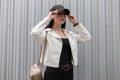 Beautiful young brunette woman with trendy gold backpack in a vintage white leather jacket in a t-shirt in black jeans. In a stylish black baseball cap posing royalty free stock photography