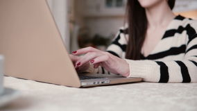 Beautiful young brunette woman uses laptop in a bright dining. slider to the right stock footage