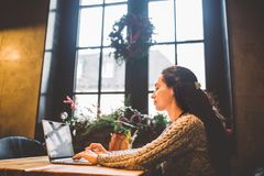 Beautiful young brunette woman using a laptop at coffee shop at a wooden table near window typing text on a keyboard. In winter, stock photography