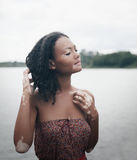 Beautiful young brunette woman with vitiligo disease. With morning lake on the background Royalty Free Stock Photo
