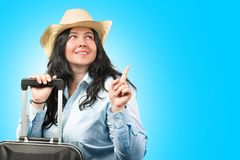 Beautiful young brunette woman wearing hat with suitcase on light blue white background. Copy space. Tourism concept royalty free stock images