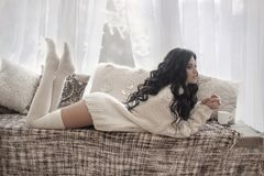 Beautiful young brunette woman wearing knitted sweater resting o Stock Photos