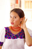 Beautiful young brunette woman wearing traditional andean white blouse with blue decorative edges, facing camera holding. Hand around ear simulating low hearing Stock Image