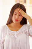 Beautiful young brunette woman wearing white blouse top, facing camera simulating headache, bright household background Stock Photo