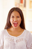 Beautiful young brunette woman wearing white blouse top, interacting screaming towards camera, bright household Royalty Free Stock Photo