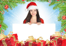 Beautiful young brunette woman with white card, gifts colorful b Royalty Free Stock Images