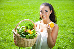 Beautiful young brunette woman with a wicker basket full of vege Royalty Free Stock Photos