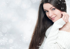 Beautiful young brunette woman-winter portrait. Beautiful young woman with shiny dark hair on winter background stock photo