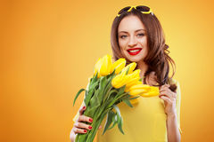 Beautiful young brunette woman with yellow tulips on yellow background Royalty Free Stock Photo