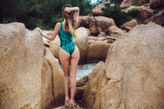 Beautiful young brunette women in blue bikini posing on the beach in turning booty shows ass. Sexy model portrait with Royalty Free Stock Image