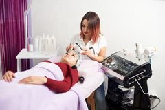 Brunette woman tightening microcurrent treatment by therapist skincare rejuvenating pampering royalty free stock images