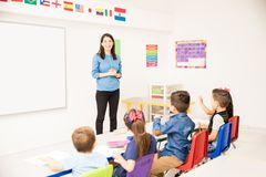 Pretty preschool teacher giving class. Beautiful young brunette working as a preschool teacher explaining something to the whole class stock image