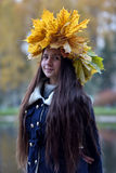 Beautiful young brunette with a wreath of autumn leaves Royalty Free Stock Image