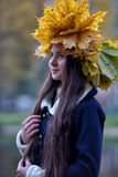 Beautiful young brunette with a wreath of autumn leaves Royalty Free Stock Photos