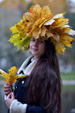 Beautiful young brunette with a wreath of autumn leaves Stock Photo