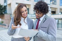 Beautiful young business couple checking some paperwork in front of the office royalty free stock photos