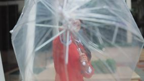 A beautiful young business lady opens an umbrella to the camera, smiles and has fun. She is dressed in a red coat stock footage