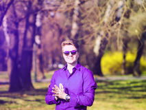 Beautiful young business man smiling and watching at the purple sky. Amazing photo of a young man in the middle of the woods Royalty Free Stock Images