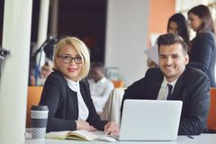 Beautiful young business partners are using a laptop, discussing documents and smiling while working in office. Royalty Free Stock Photo
