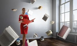 Beautiful young business woman with books. Mixed media. Beautiful young business woman with books in a work room. Mixed media royalty free stock photos
