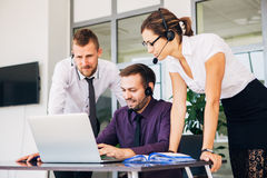 Beautiful young business woman and businessmans in headsets using laptops while working in office Stock Image