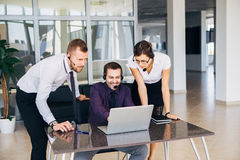 Beautiful young business woman and businessmans in headsets using laptops while working in office Stock Photo