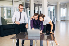 Beautiful young business woman and businessmans in headsets using laptops while working in office Royalty Free Stock Photo
