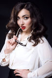 Beautiful young business woman with dark wavy hair and red lips wearing white silk blouse keeping the side of glasses in her mouth royalty free stock image