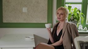 Beautiful young business woman is drinking coffee in a coffee shop. Beautiful young business woman is drinking coffee in a coffee shop stock footage