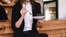 Beautiful young business woman eating a cake with a spoon in a cafe on a bar counter background. stock video footage